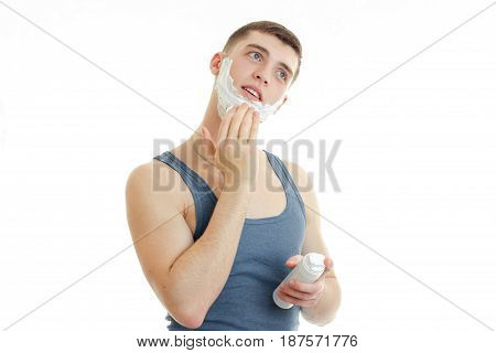 handsome young guy in a t-shirt worth bending head and putting foam face isolated on white background