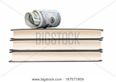 Money rolled into a tube and strapped a rubber band lying on top of a stack of three books