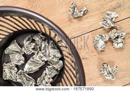 Crumpled dollars on a wooden table and in a plastic trash can close up