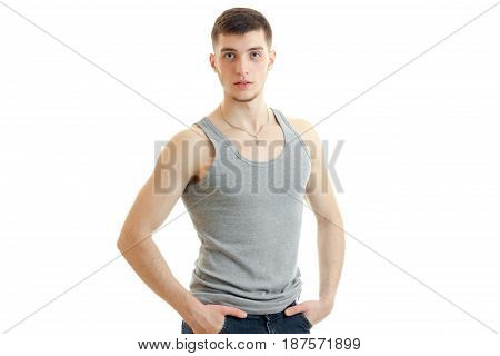 handsome young guy standing in a t-shirt and keeps his hands in his pockets is isolated on a white background