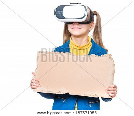 Happy little girl wearing virtual reality goggles watching movies or playing video games. Child with VR glasses and corrugated cardboard torn pieces.