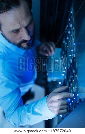 Everything must be in order. Nice professional male technician pressing the button on the network server and checking the settings while working in the server room