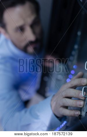 Network server check. Selective focus of a hand of a professional male technician while checking the network server