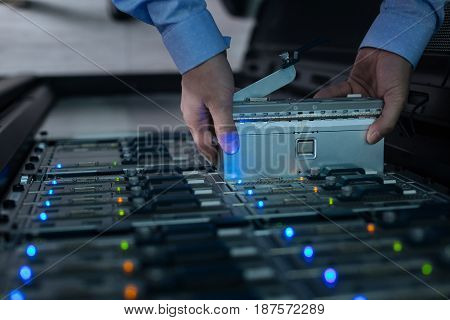 Data storage. Close up of a rack server being taken out of the data storage by a professional male technician