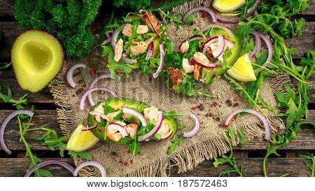 Avocado boats stuffed with salmon, red onion and arugula. concept healthy food.