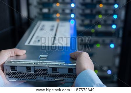 Internet communications. Selective focus of a rack server being help by a professional experienced IT administrator