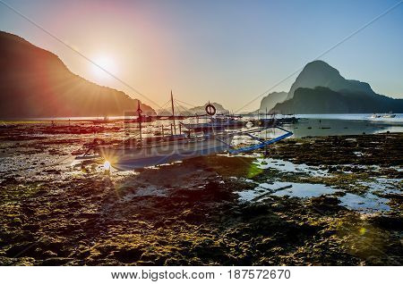 Banca local boats during low tide. Sunrise and amazing shape of rocks of Cadlao Island in background, El-Nido, Palawan, Philippines.