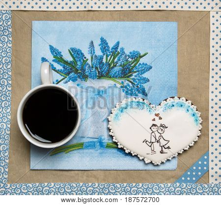 Gingerbread heart in a frame with cup of coffee. Craft paper background. St. Valentine gift