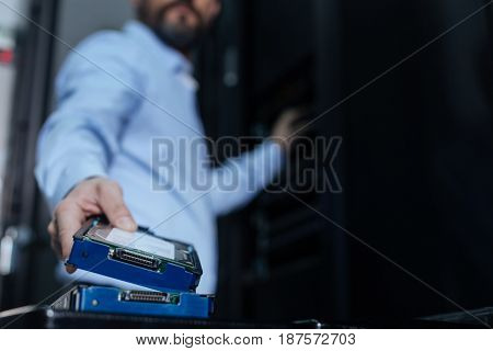 Information storage. Selective focus of a rack server being taken by a handsome good looking male programmer while standing in the data center