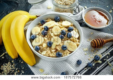 Bowl of Healthy Breakfast oatmeal with ripe blueberries, banana, honey, almonds
