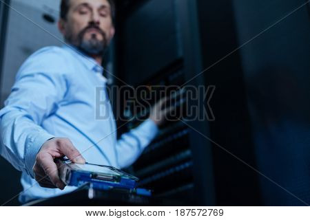 Professional technician. Handsome nice bearded programmer taking a rack server and intending to install it while working in the data center
