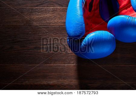 Close-up of a pair of boxing blue and red gloves hanging on the wooden wall. Horizontal photo and brown wooden background. Boxing backgrounds and still-life. Training and sportive exercise. Concept of the active lifestyle.