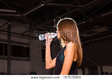 Fitness woman drinking water from bottle. Muscular young female at gym taking a break from workout