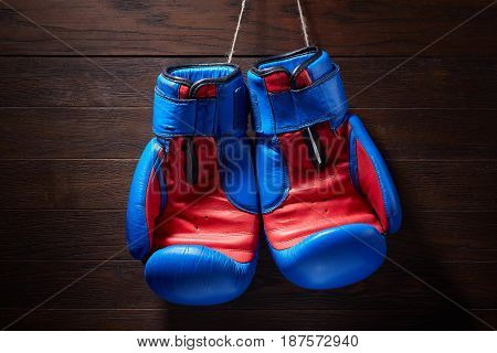 Boxing blue and red gloves hanging from ropes on a wooden background. Horizontal photo of the bright sportwear against brown wall. Boxing backgrounds and still-life. Concept of the active lifestyle.