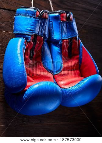 A pair of red and blue boxing gloves hang against wooden wall. Vertical photo of the bright colorful sportwear against brown background. Boxing backgrounds and still-life. Sportive exercise and training. Concept of the active lifestyle.
