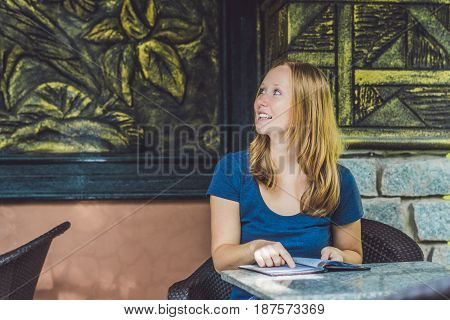Beautiful Woman Ordering From Menu In Restaurant And Deciding What To Eat