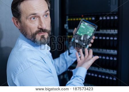 Data saving. Handsome pleasant bearded man holding a hard drive and pointing at it while standing near the server rack