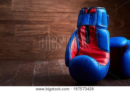 Close-up of the pair of red and blue boxing gloves on the wooden plank. Horizontal photo of colorful sportwear against brown background. Boxing backgrounds and still-life. Concept of the sportive lifestyle.