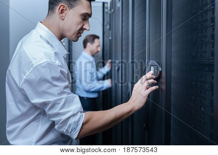 Security check. Nice handsome delighted man looking at the indicator panel and pressing the button while entering the code