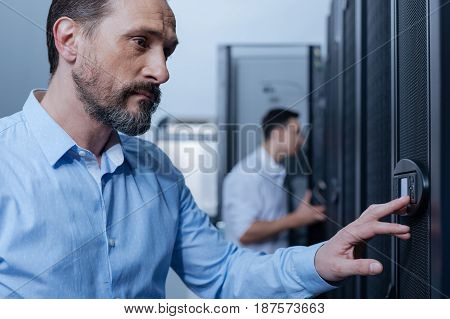 Security protection. Handsome nice adult man entering the code and pressing the button on the control panel while opening the door