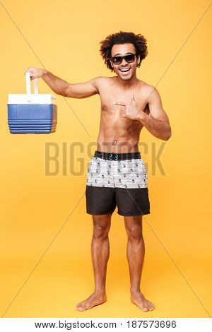 Full length portrait of a young afro american man in summer shorts holding and pointing at icebox over yellow background