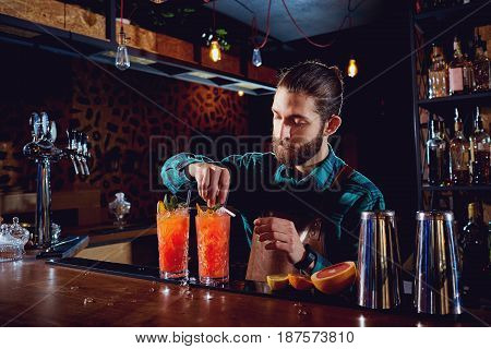 Bartender with a beard makes a cocktail behind counter in the bar.