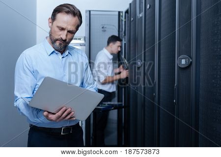 Internet network. Nice serious male programmer looking at the laptop screen and checking the work of Internet servers while standing in the middle of the data center