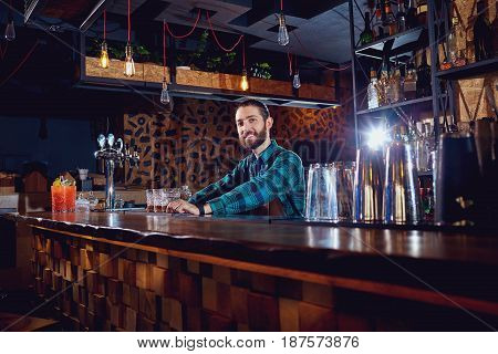A barman with  beard behind counter in the bar.