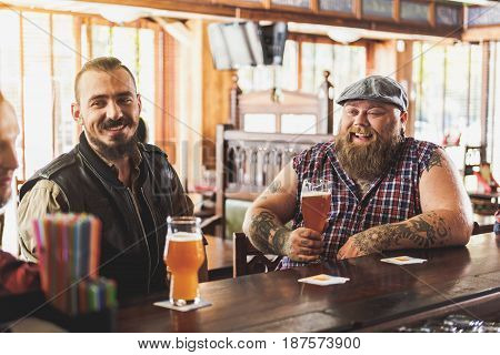 Fun together. Cheerful bearded guys sitting in pub. They drinking beer and laughing