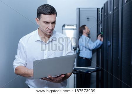 Modern device. Pleasant nice young programmer holding a laptop and using it while examining the work of internet servers