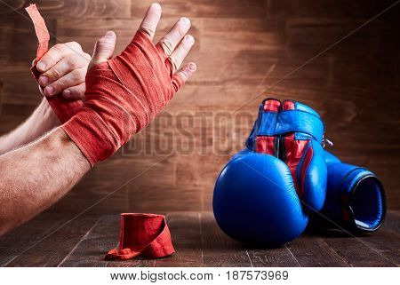 Sportive man wrapping her hands with bandage tape and boxing gloves on wooden plank. Horizontal photo. Colorful boxing equipment. Boxing training and exercise. Concept of the sportive lifestyle.