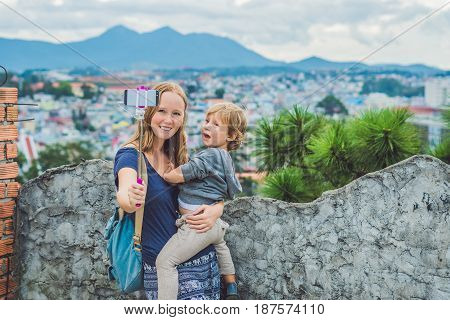 Young Woman And Her Son Taking Smart Phone Self Portrait Pictures With Selfie Stickon The Background