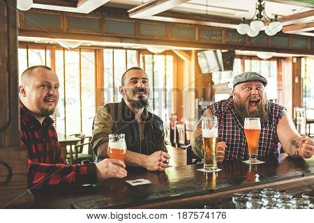 It is goal. Three happy bearded men in casual wear drinking beer and screaming. They watching football match in bar together