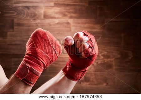 Close-up of hands with red bandage of boxer ready for a fight against wooden wall. Horizontal photo and brown background. Boxing exercise and training. Energy, power and victory. Concept of the sportive lifestyle.