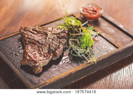 Juicy meat. Close-up of grilled T-bone steak with mix salad and tomato sauce on wooden plate. Focus on spicy meat