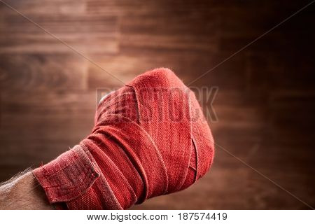 Close up image of fist of a boxer with red bandage against brown background. Horizontal photo and wooden wall. Boxing equipment. Sportive exercise and training. Power, energy and victory. Concept of the sportive lifestyle.