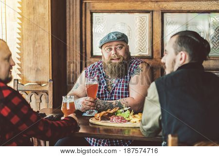 Enjoying rest. Three adult bearded men sitting in pub and talking with smile. They drinking beer with potato crisps