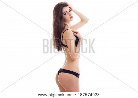 sexy young girl with long hair stands in underwear stretched sideways in front of a camera isolated on white background
