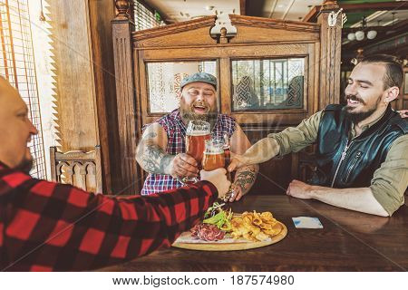 Male company. Pleasant positive nice men cheering with glasses and smiling while meeting in pub. They talking and enjoying cold beer