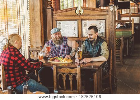 After difficult day. Cheerful bearded men sitting around table and talking while relaxing in pub. They drinking cool beer with snacks