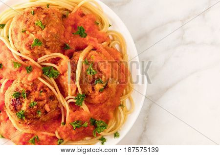 A closeup of a plate of meatballs with pasta, tomato sauce, and fresh parsley, shot from above on a white marble texture with a place for text