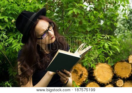 The girl in the Park reading a book amongst the trees