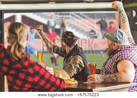 Football time. Old friends spending time together in pub. Guys having fun while watching football and screaming