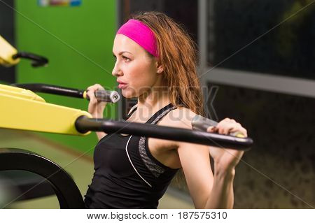 Sexy fitness girl exercising at the fitness gym. Make exercise with sports simulator