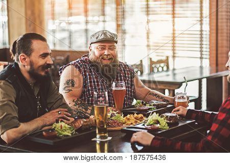 Friendly atmosphere. Smiling fat man sitting with his friends at table and enjoying his dish. He looking at camera with joy
