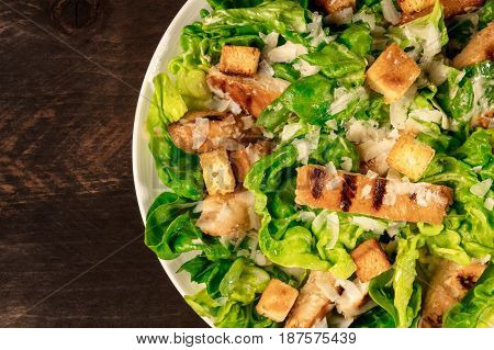 A closeup of a plate of chicken Caesar salad, shot from above on a dark rustic background with a place for text