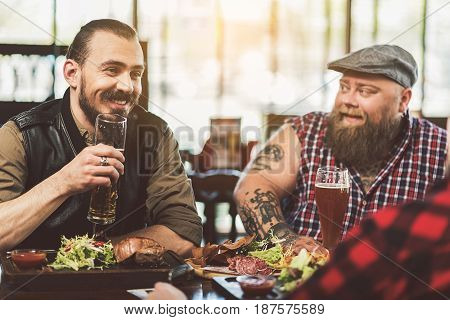 Drinking together. Handsome joyful bearded man holding glass with beer and talking with his friends while sitting in pub. Selective focus of dark brown haired guy