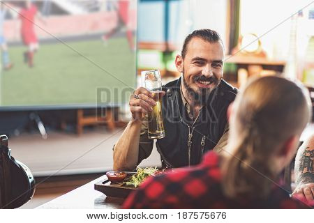 Positive atmosphere. Pleasant handsome man clinking with his friends and smiling. They resting in pub while watching football