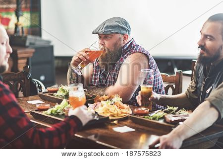 Pleasant time with friends. Stylish bearded men enjoying cool beer while having dinner together. Focus on fat tattooed guy with glass of ale