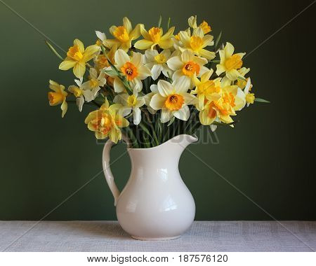 The varietal bouquet of yellow daffodils in a white jug on a green background.